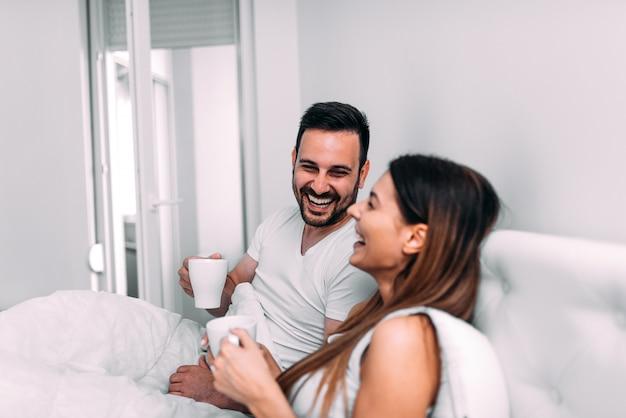 Couple, lit, boire café, rire