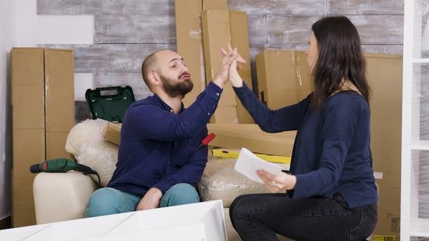 Un couple lit des instructions pour l'assemblage de meubles dans une nouvelle maison. une fois le travail terminé, ils font un high five.