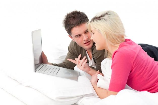 Couple sur le lit avec un ordinateur portable