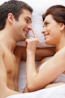 Couple ludique au lit. vue de dessus du beau jeune couple d'amoureux allongé dans son lit pendant que la femme touche le nez de son petit ami