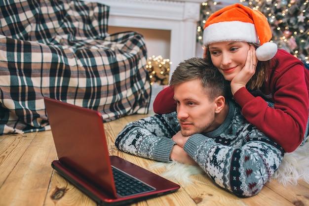 Couple ludique au sol. jeune femme allongée sur le dos de l'homme. ils regardent sur l'écran de l'ordinateur portable. elle sourit. ils s'amusent.