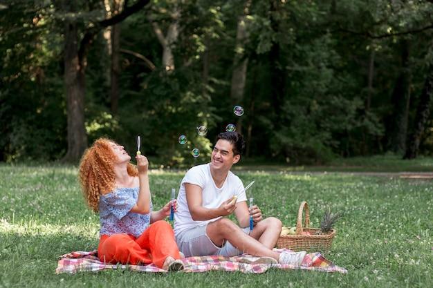 Couple ludique faisant des bulles dans le parc