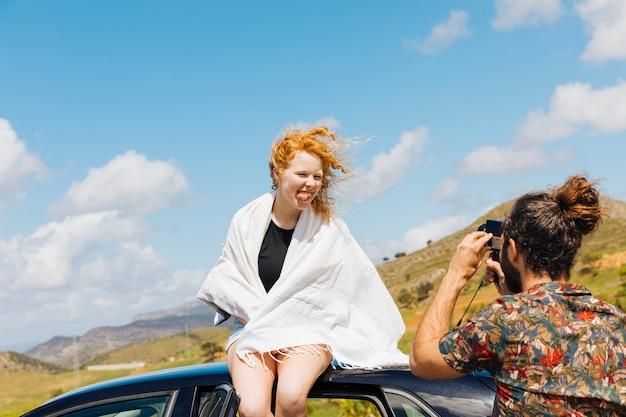 Couple ludique prenant des photos sur le toit de la voiture