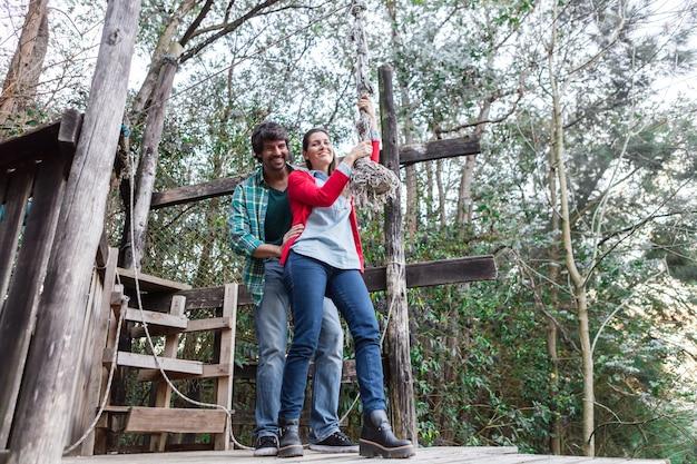 Couple ludique tenant la corde dans le parc d'aventure