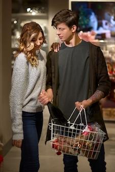 Couple lumineux souriant, acheter du champagne avec panier dans un supermarché