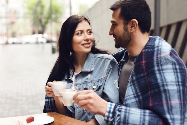 Couple en lune de miel dans un café enveloppé dans une couverture douillette.