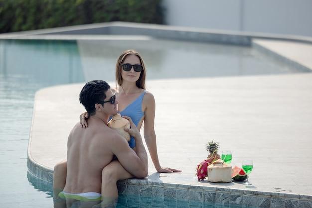 Couple de lune de miel heureux temps dans la piscine, couple d'homme et fille en bikini de sous-vêtements de mode doux