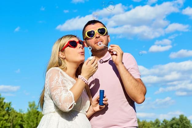 Couple à lunettes de soleil soufflant des bulles de savon l'été contre un bleu