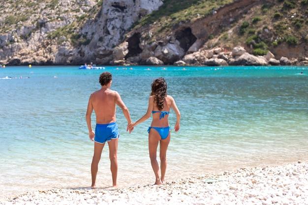 Couple en maillot de bain bleu sont debout dans l'eau sur la plage de pierre.