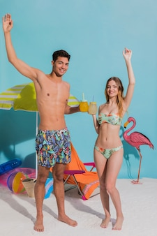 Couple en maillot de bain buvant des cocktails