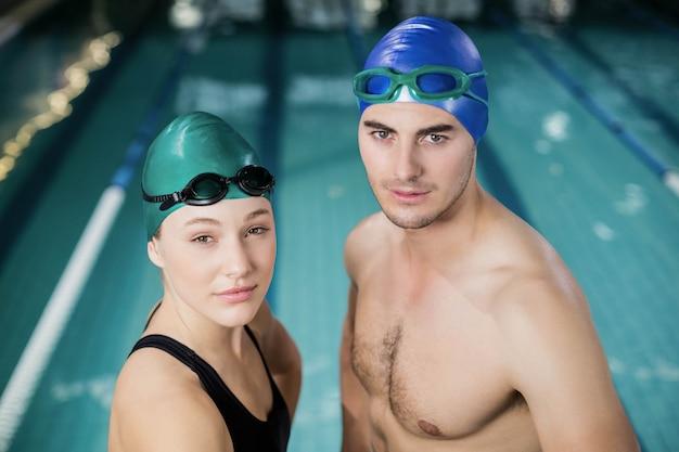 Couple en maillot de bain en regardant la caméra à la piscine