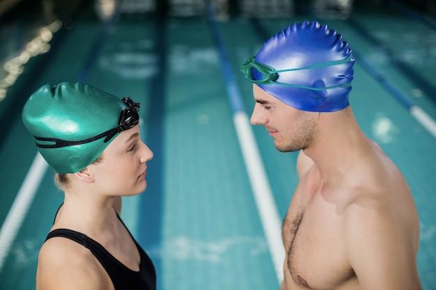 Couple en maillot de bain se regardant les uns les autres à la piscine