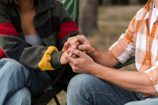 Couple main dans la main à l'extérieur en camping