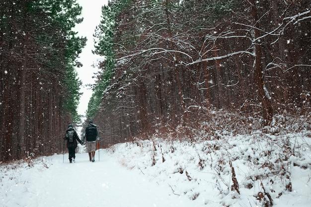 Un couple main dans la main en marchant sur une belle journée d'hiver