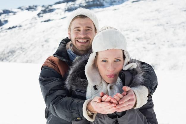 Couple avec les mains en coupe sur un paysage enneigé