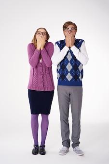 Couple avec les mains couvrant leur bouche isolé