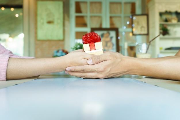 Un couple de mains tenant une boîte-cadeau or avec ruban rouge au restaurant.