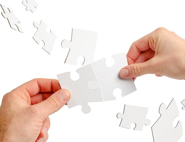 Couple de mains tenant le puzzle isolé sur blanc. concept de collaboration d'équipe et d'entreprise.
