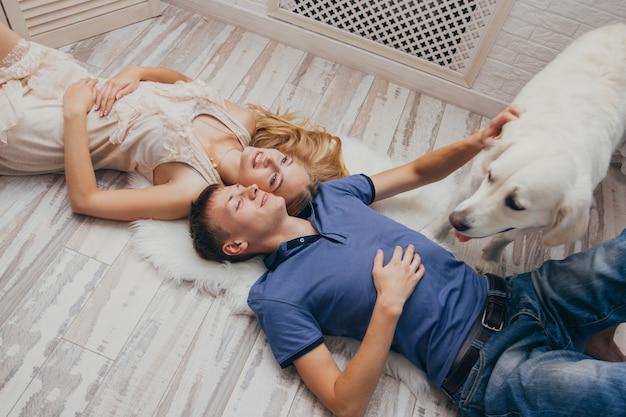 Couple à la maison allongé sur le sol avec son chien