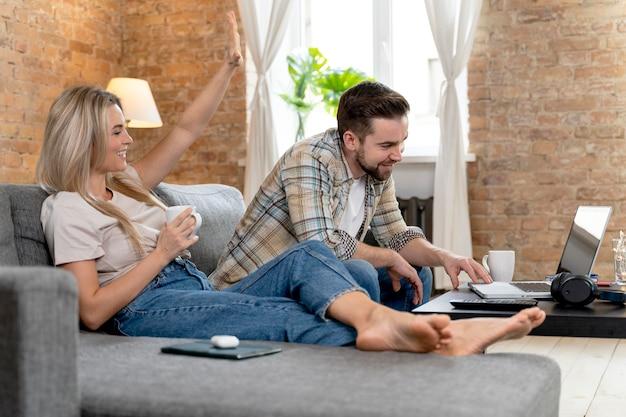 Couple à la maison ayant un appel vidéo avec la famille