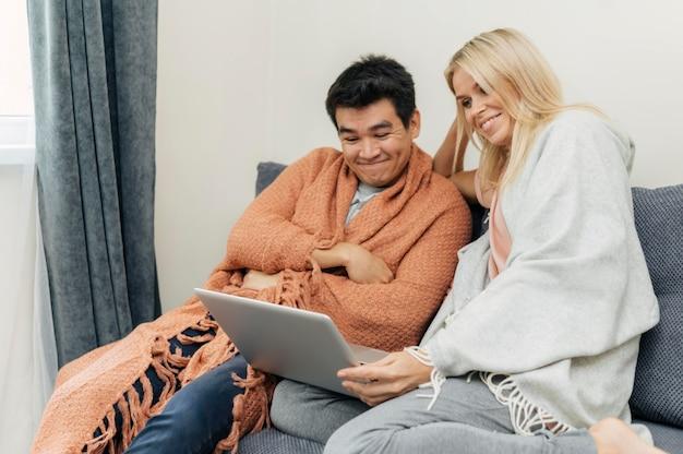 Couple à la maison ensemble à l'aide d'un ordinateur portable sur le canapé