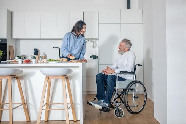 Couple à la maison. jeune femme faisant le petit déjeuner, son mari handicapé s'asseyant près