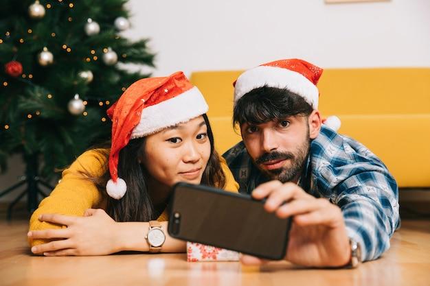 Couple à la maison prenant selfie à noël