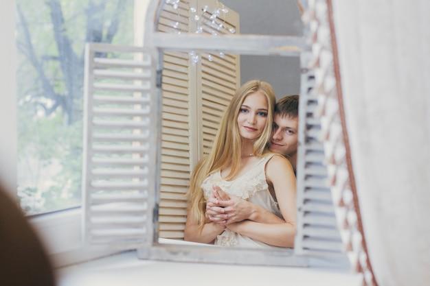 Couple à la maison regardant dans le miroir près de la fenêtre