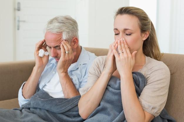 Couple malade assis sur le canapé sous une couverture