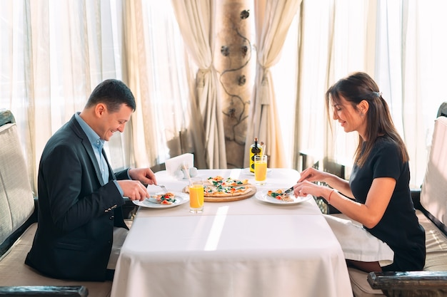 Un couple mange de la pizza dans un restaurant.