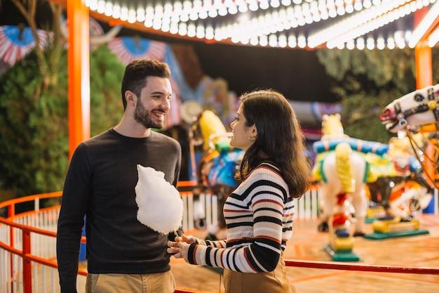 Couple mangeant une barbe à papa dans un parc à thème
