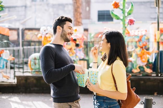 Couple mangeant du maïs soufflé dans un parc à thème