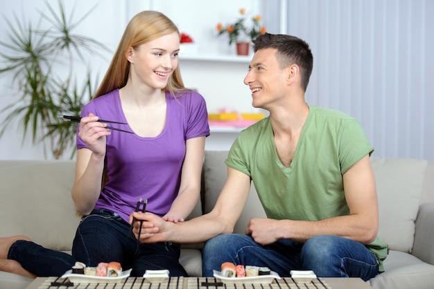 Couple mangeant des sushis assis près l'un de l'autre.