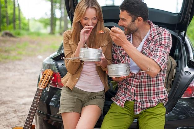 Couple de manger dans la voiture avant de partir en randonnée
