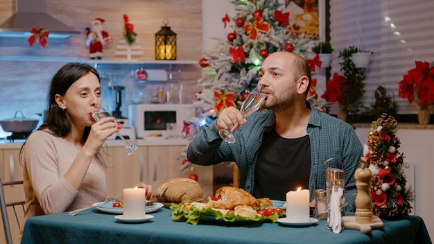 Couple de manger de la nourriture au dîner de fête et des verres tintants