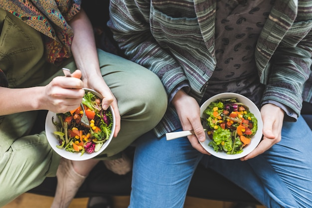 Couple, manger sainement, salade, maison, sofa