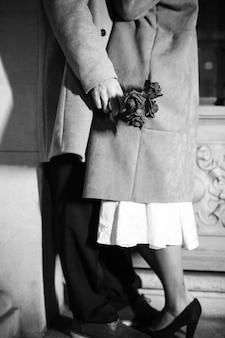 Couple en manteaux s'embrasser se penchant sur le mur du bâtiment