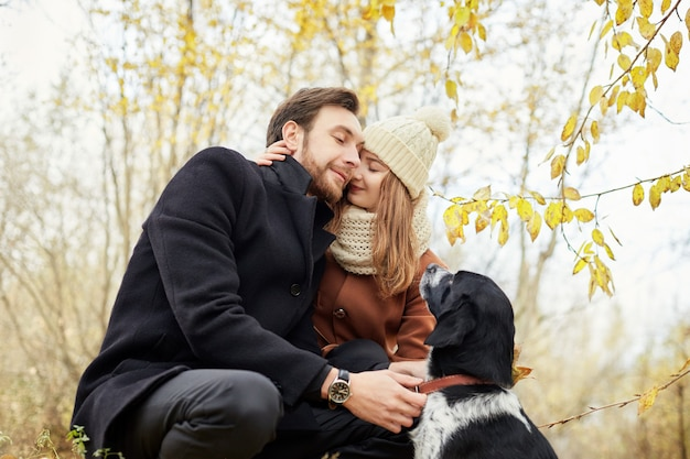 Couple marchant avec un chien dans le parc et s'embrassant. promenade d'automne en bois hommes et femmes avec un chien. romance et amour sur un paysage d'automne. famille se reposant dans la nature