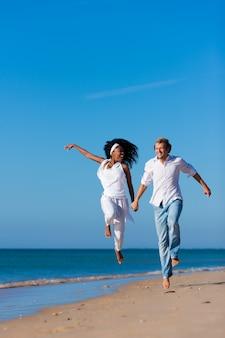 Couple marchant et courant sur la plage