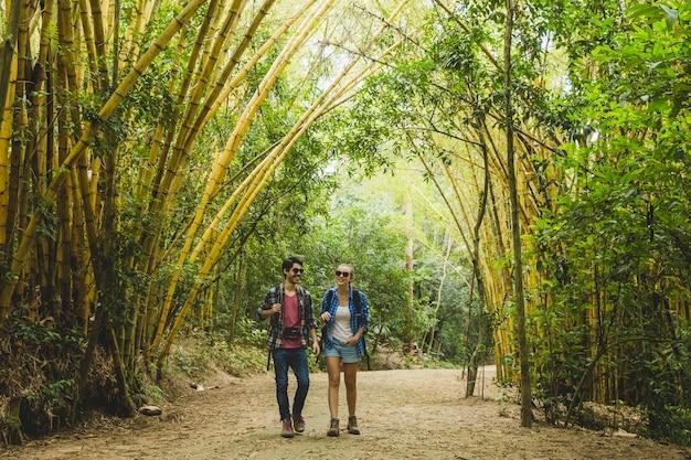 Couple marchant dans la forêt de bambous
