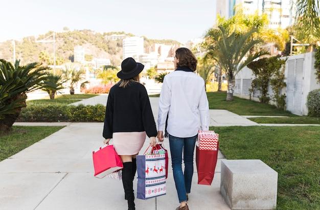Couple marchant dans le parc avec des sacs