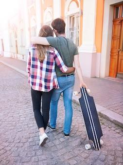 Couple marchant dans la ville. un rendez-vous romantique. homme patineur.