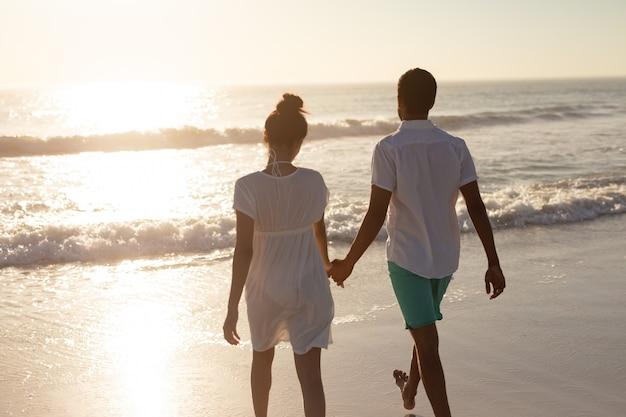 Couple marchant ensemble main dans la main sur la plage