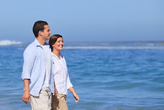 Couple marchant sur la plage sous le soleil