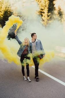Couple marchant sur la route en montagne tenant la fumée colorée jaune dans les mains.