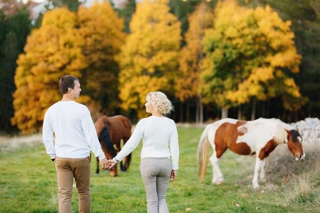 Couple marche sur la pelouse dans la forêt d'automne main dans la main des chevaux paissent sur la pelouse vue arrière