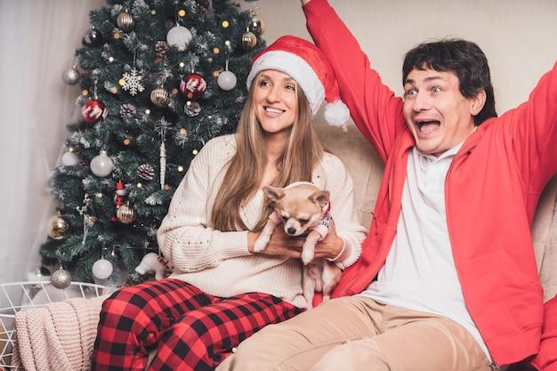 Couple mari et femme regardant la télévision profiter à noël.