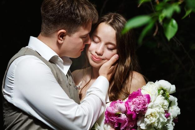 Couple de mariage aimant s'embrasser dans le parc