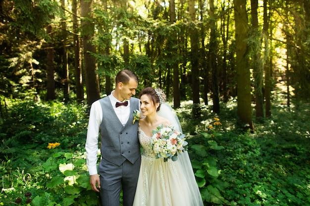 Un couple de mariage aime se promener dans les bois. les nouveaux mariés s'enlacent et se tiennent la main