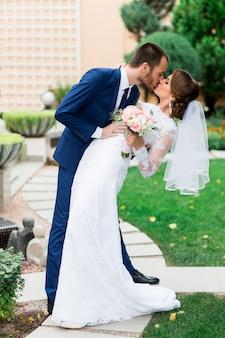 Couple de mariage amoureux s'embrassant et souriant. jeune mariée assez élégante et son beau marié posant dans le parc verdoyant.